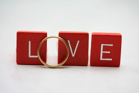 Red wooden letters with a simple yellow gold wedding band.