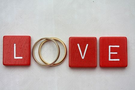 Red wooden letters with simple plain wedding bands. photo