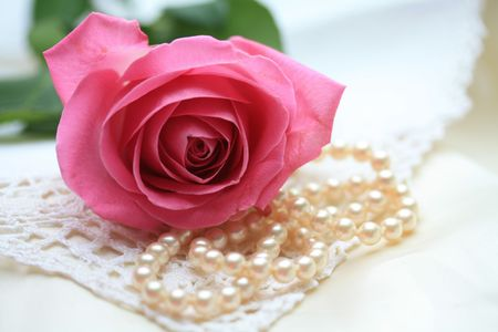 A pink rose on a pearl necklace and some lace photo