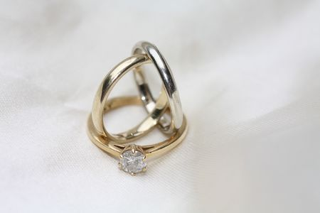 two simple plain wedding bands and a diamond solitaire engagement ring Stock Photo