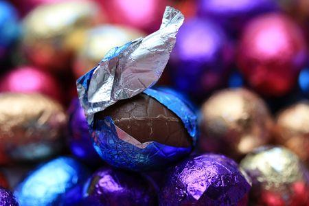 huevos fritos: Un huevo de Pascua de chocolate en un envoltorio azul sobre un fondo de chocolate huevos de Pascua Foto de archivo
