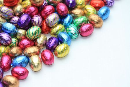 A pile of colored easter chocolate eggs with copy space