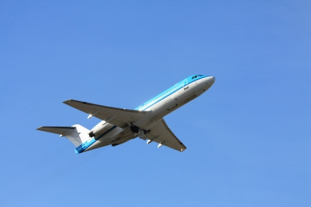 departing: A two engine aircraft departing in a clear blue sky