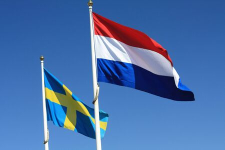 Two flags in the wind, Swedish and Dutch flag photo