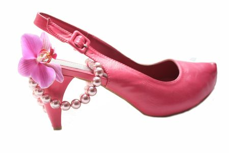 A pink high heel ladies shoe, a pearl necklace and an orchid photo