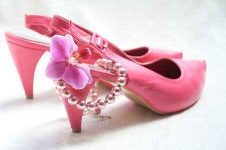 A pair of pink leather ladies shoes, a pink orchid and a pearl necklace Stock Photo - 7092863
