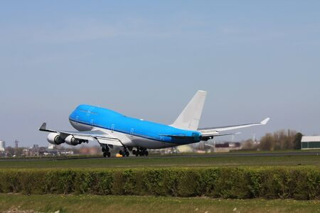 A big airplane taking off: loads of heat coming from the four engines and only some wheels on the ground photo