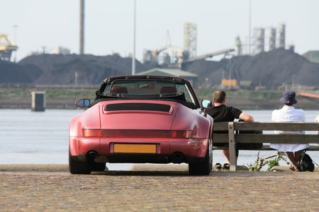 A senior couple enjoying the view on the waterside, their open vintage convertible parked aside photo