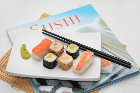 tunafish: A traditional oblong Japanese plate with a variety of sushi on top of a Sushi book