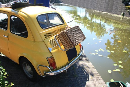 italian car: A small Italian car with a wicker suitcase on the back Stock Photo
