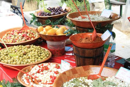 A variety of French delicacies like olives, tapenade and marinated garlic on a local market in Bedoin, France