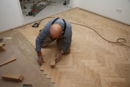 Man laying a wooden parquetry flooring in fishbone pattern photo