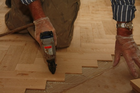 Detail of a man busy laying a wooden floor in fishbone pattern