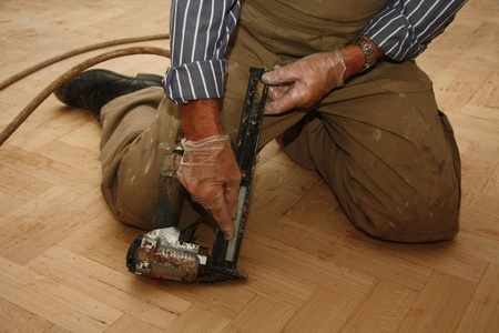 artisanry: Refilling an electric stapler while laying a wooden floor Stock Photo