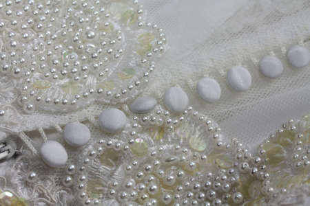bridal gown: Detail of a white bridal gown or wedding dress with pearls and white buttons