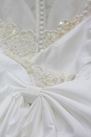 Detail of a white bridal gown or wedding dress with pearls and white buttons