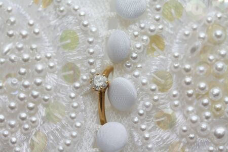 A yellow golden diamond ring on a wedding dress photo