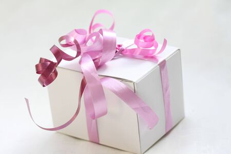 A white gift box with pink ribbons photo