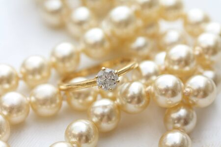 A solitaire diamond engagment ring on a pearl necklace Stock Photo - 9055077