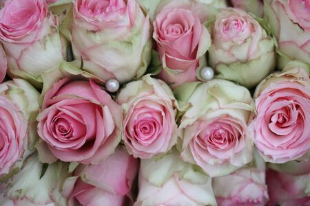 Pearls and pinkwhite roses in a bridal bouquet