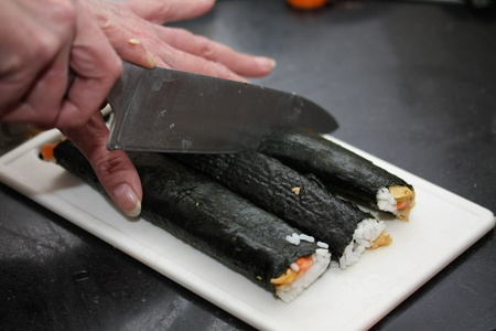 Cutting makisushi: fish, rice and other ingredients rolled in seaweed photo