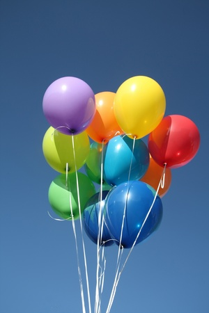 Colorful balloons dancing in a blue sky photo