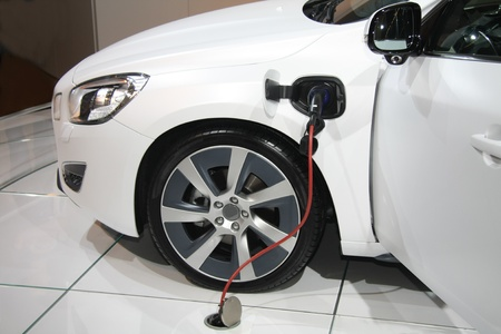 A white electric hybrid car on recharge photo