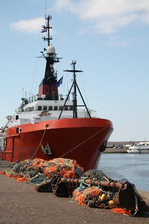 An orange fishing trawler and nets in the harbour photo