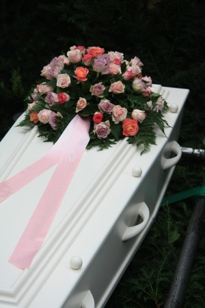 A multicolored pink sympathy bouquet with pink ribbon on a white coffin Stock Photo