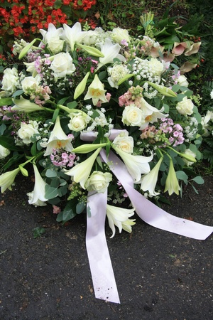 A white sympathy floral arrangement near a grave