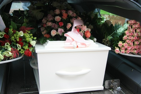 mortality: A white coffin, covered with flowers in a grey hearse Stock Photo