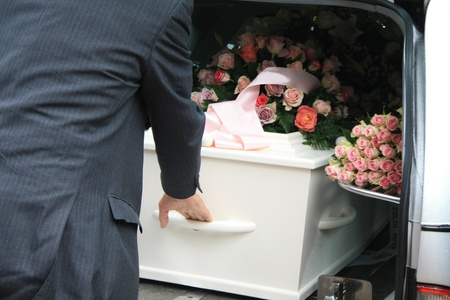 A funeral home employee takes out a white coffin of a hearse photo