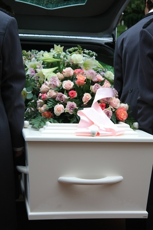 coffin: A white coffin, covered with flowers near a hearse, people taking out the coffin