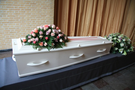 A whtie coffin with pink flowers at a funeral service