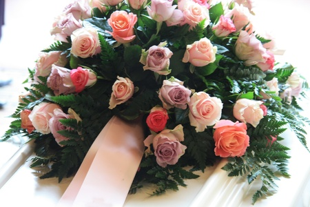 pink sympathy flowers with a pink ribbon on a white coffin