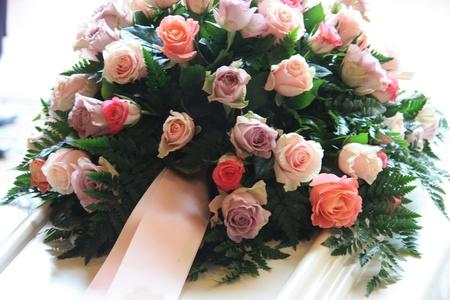Rosa Anteilnahme-Blumen mit einem rosa Band auf einem weißen Sarg