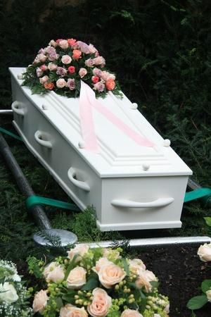 Weißen Sarg und mehrere Sympathie Blumenschmuck auf einem Grab Seite