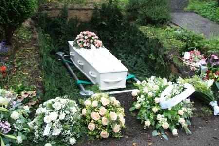 White coffin and several sympathy floral arrangement on a grave side photo