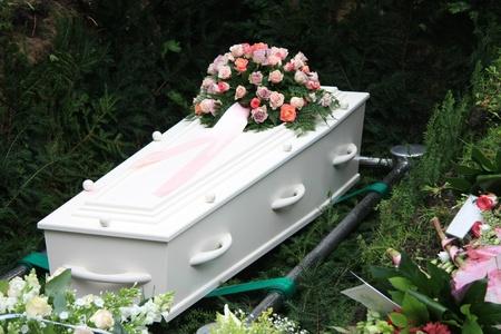 白い棺および墓の側にいくつかの同情生け花