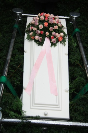 White casket with mixed pink sympathy flowers and pink ribbon photo