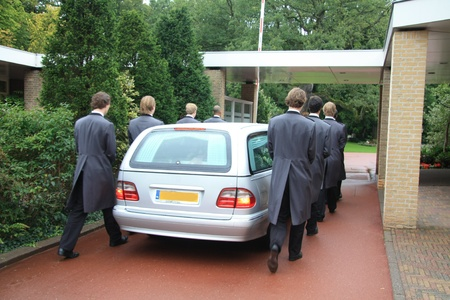 A grey hearse and funeral servants entering a cemetery Stock Photo