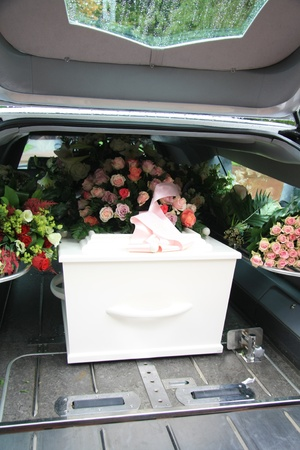 funeral: White casket covered with floral arrangements in a hearse