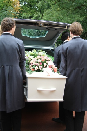 Funeral home employees take out a white casket of a hearse