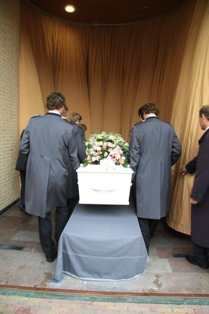 Funeral home employees preparing a casket for a funeral service photo