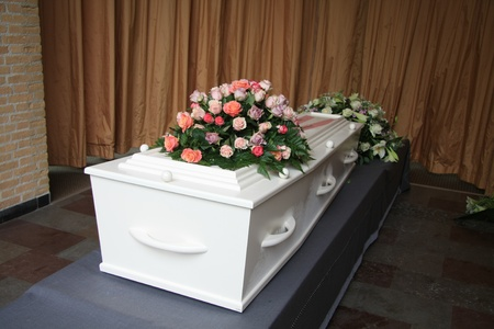 casket: White casket covered with floral arrangements at a funeral service