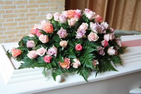 Ataúd blanco cubierto de arreglos florales a un funeral Foto de archivo