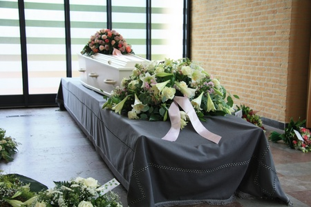 burial: White casket covered with floral arrangements at a funeral service
