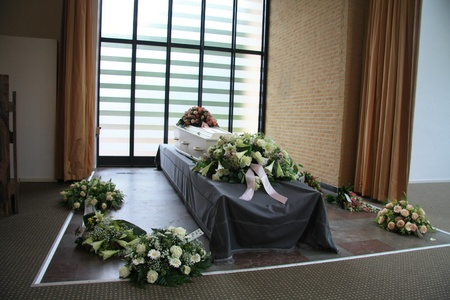 coffin: White casket covered with floral arrangements at a funeral service