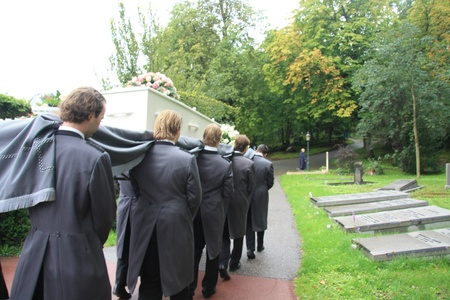 Employees of a funeral home bring a white casket to a grave