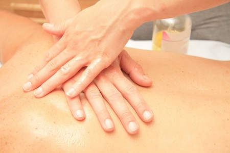 A female masseur giving massage, detail of hands on back Stock Photo